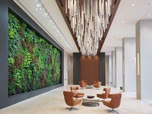 Sala de espera con mesas y sillones. en la pared hay un gran gardín vertical. Biofilia.